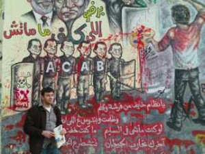 "War Resister staff person Ali Issa in front of a mural stating, in part: ""Oh regime which is scared of a paintbrush and a pen. You oppress us … If you were doing what you should be doing, you wouldn't be afraid."" (photo by Tamar Sharabi)"